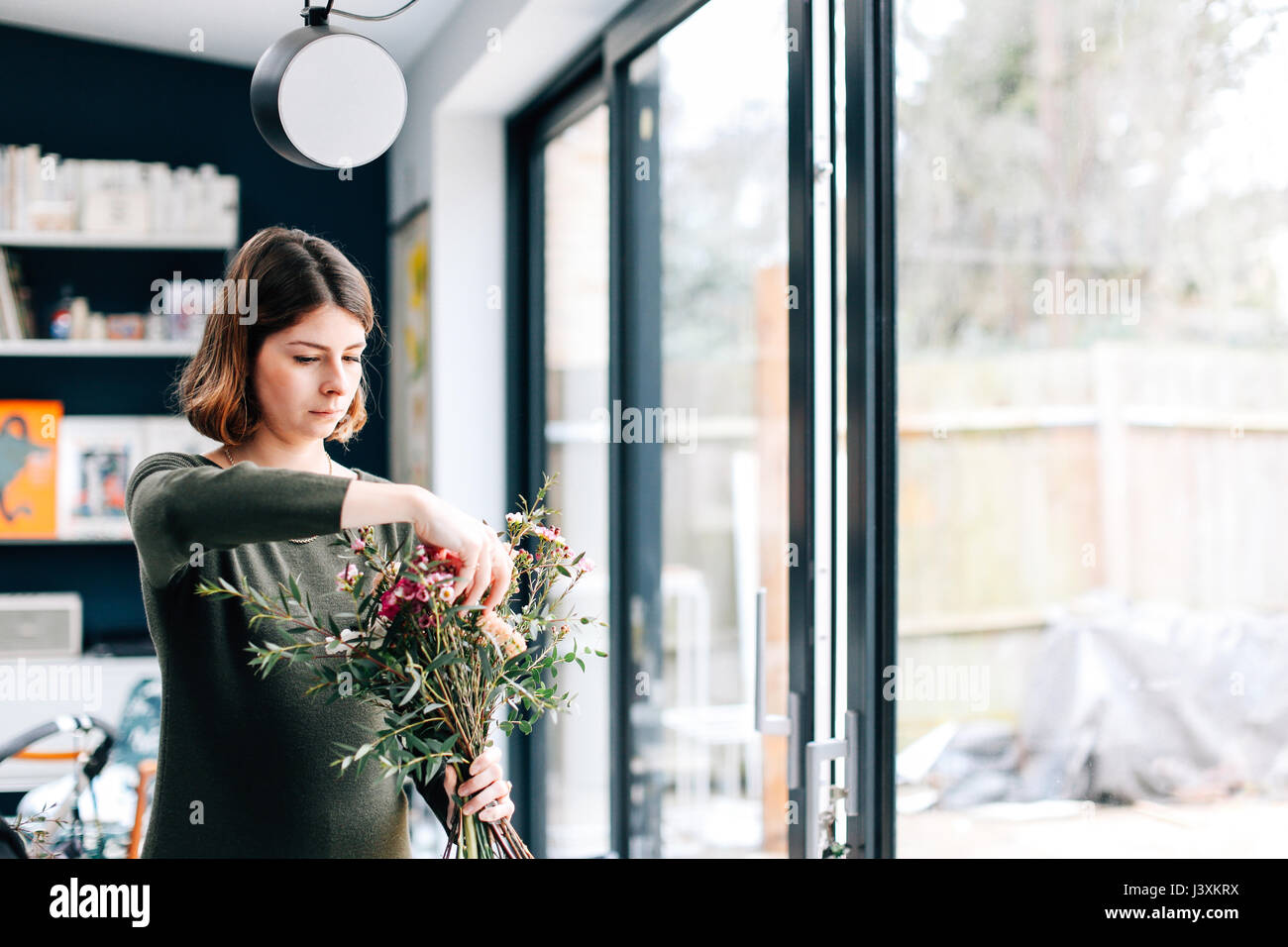 Florist student arranging bouquet at flower arranging workshop - Stock Image