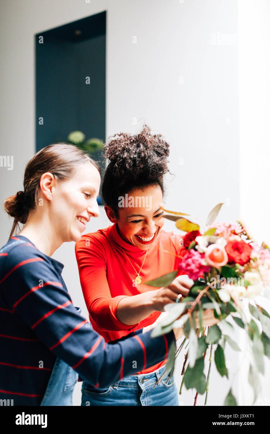 Florist and student arranging bouquet at flower arranging workshop - Stock Image