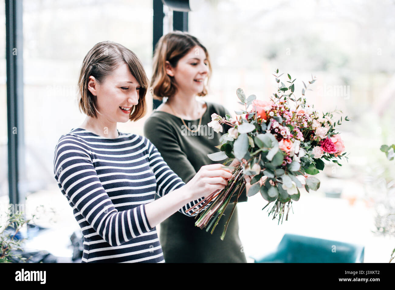 Florist students arranging bouquets at flower arranging workshop - Stock Image