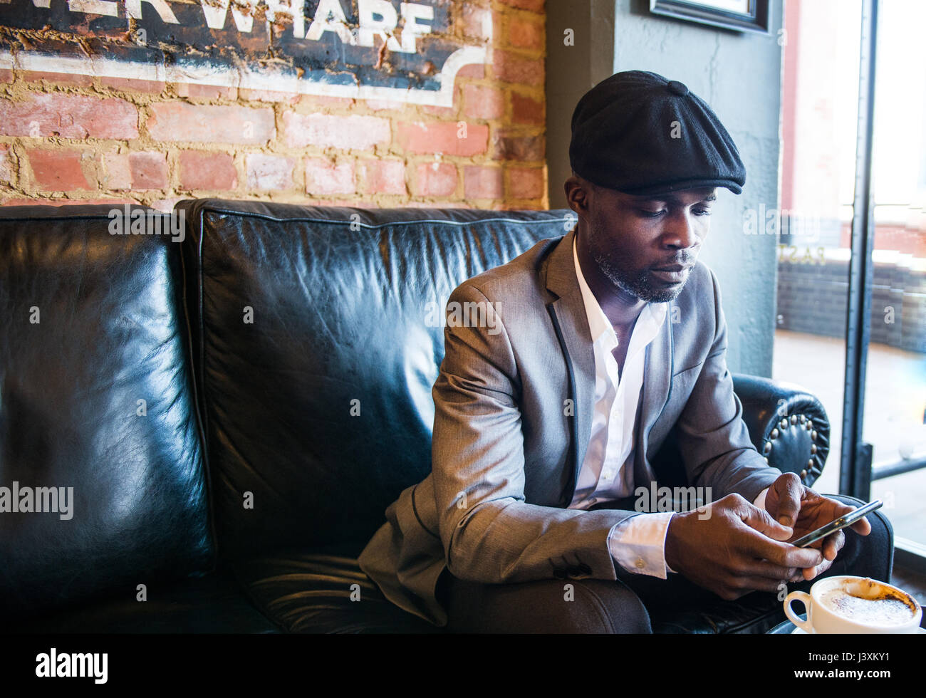 Businessman texting on sofa in cafe, London, UK - Stock Image