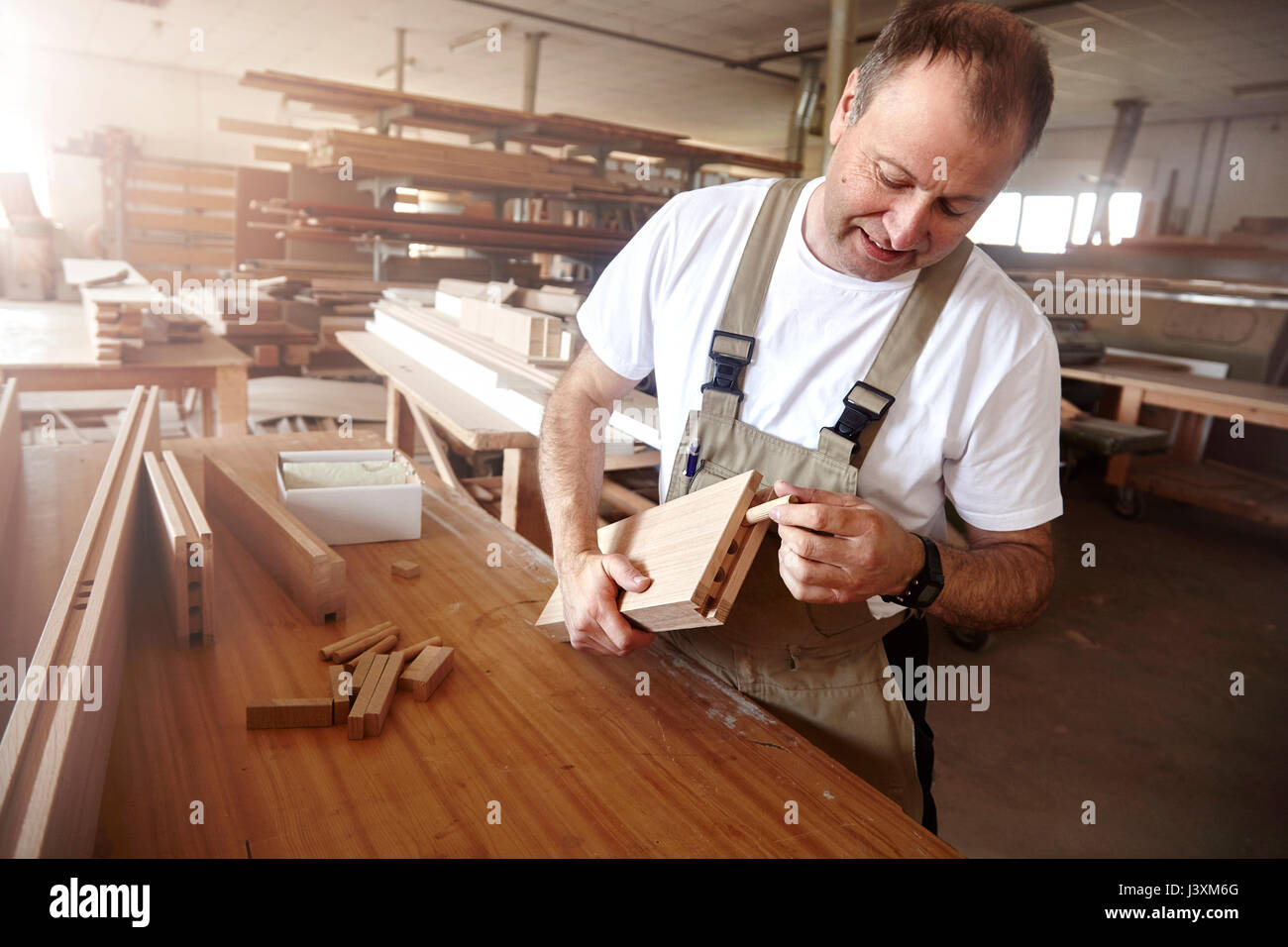 Male carpenter inserting wooden dowel at workbench - Stock Image