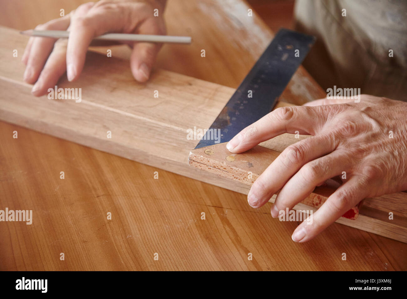 Hands of male carpenter using set square at workbench - Stock Image