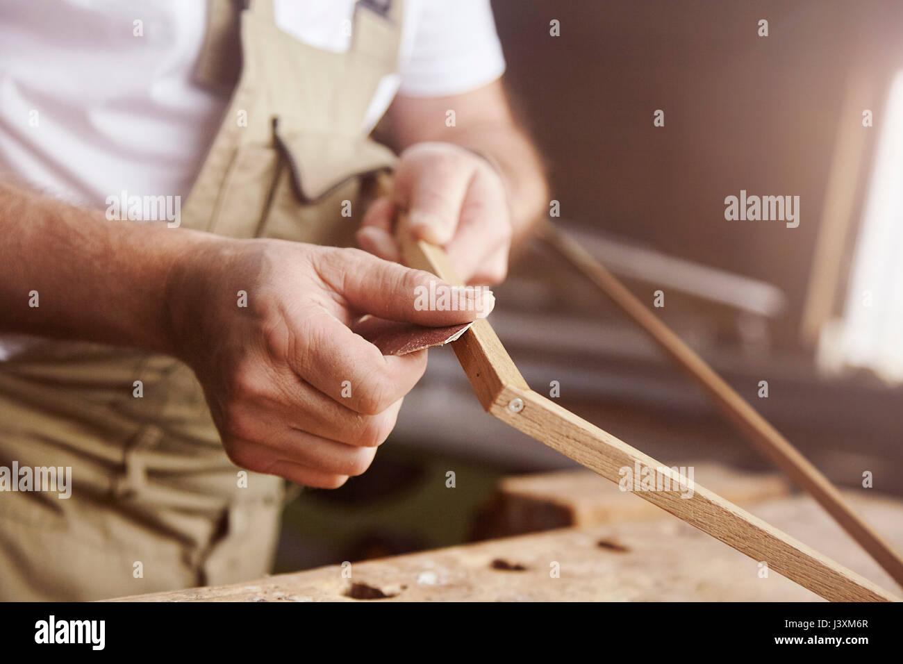 Hands of male carpenter sanding frame at workbench Stock Photo