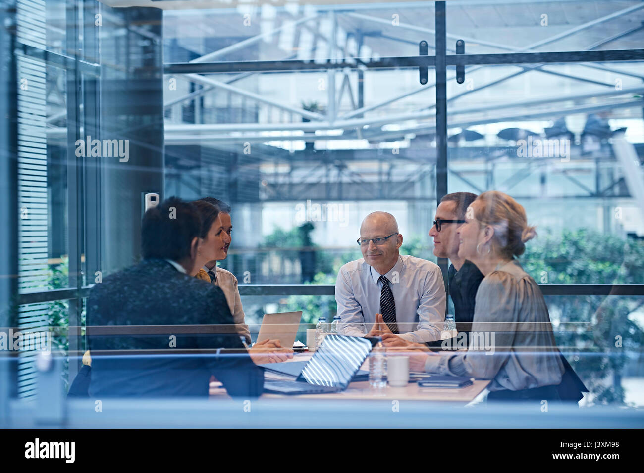 Window view of businesswomen and men having discussion in conference room - Stock Image
