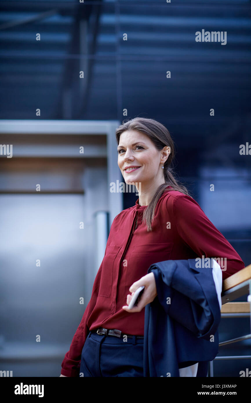 Businesswoman leaning on office handrail holding smartphone - Stock Image