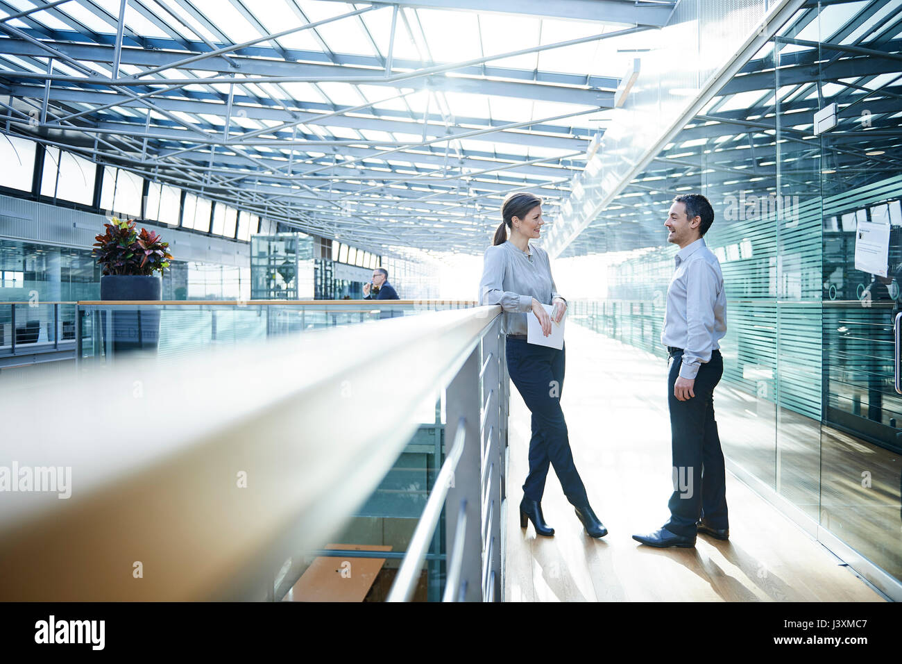 Businessman and woman talking on office balcony - Stock Image
