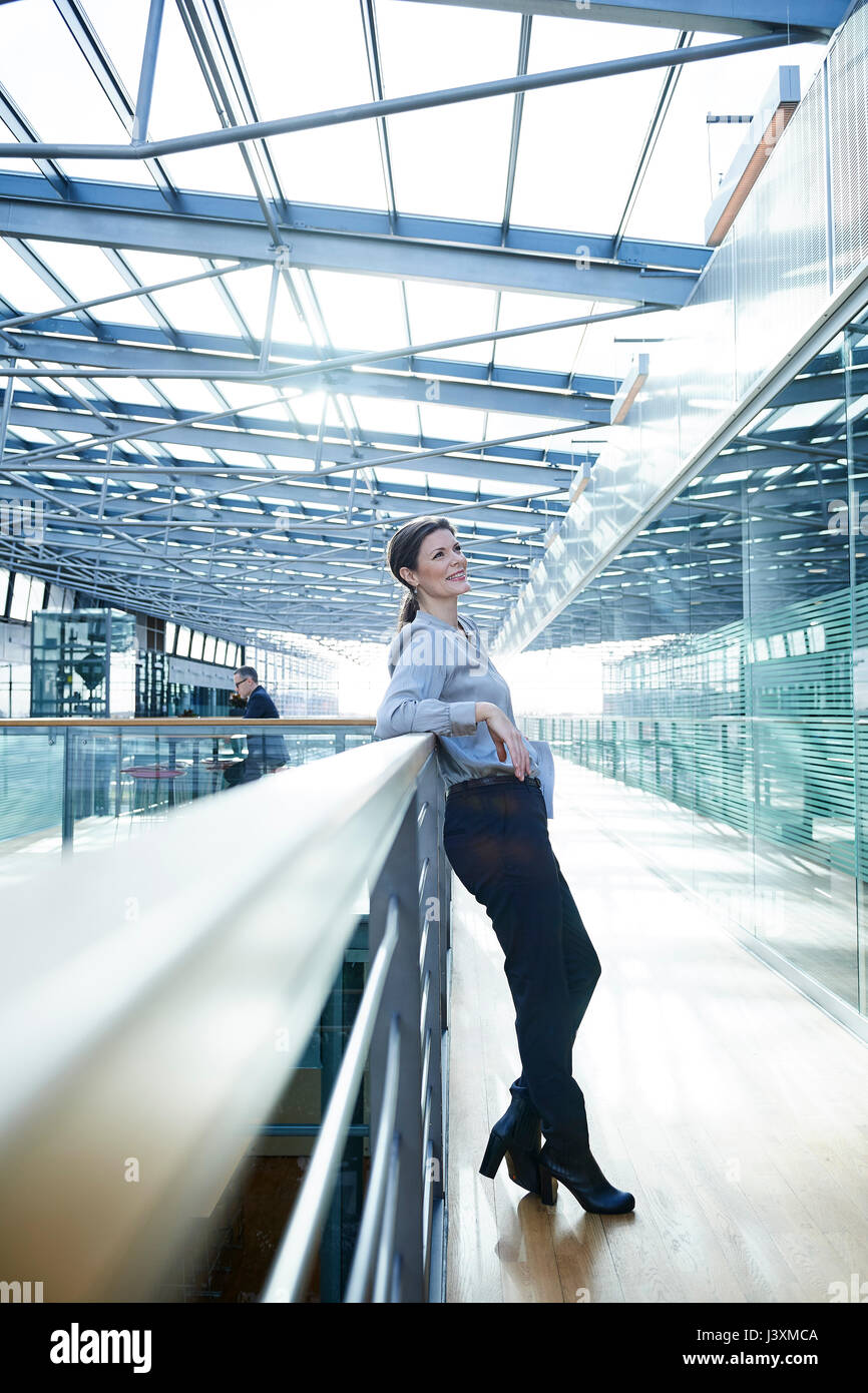 Happy businesswoman leaning against office balcony - Stock Image