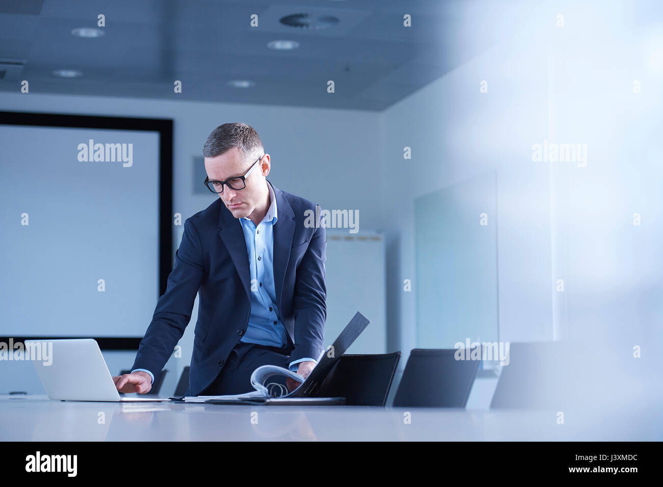 Businessman typing on laptop at boardroom table - Stock Image