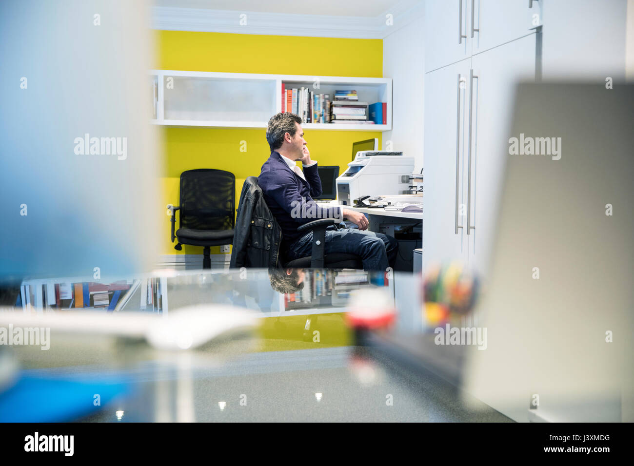 Man sitting at desk in office making telephone call - Stock Image