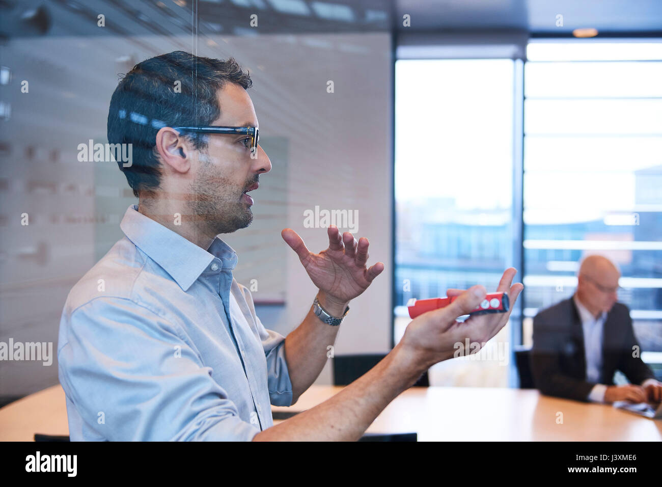 Window view of businessman making presentation in office - Stock Image