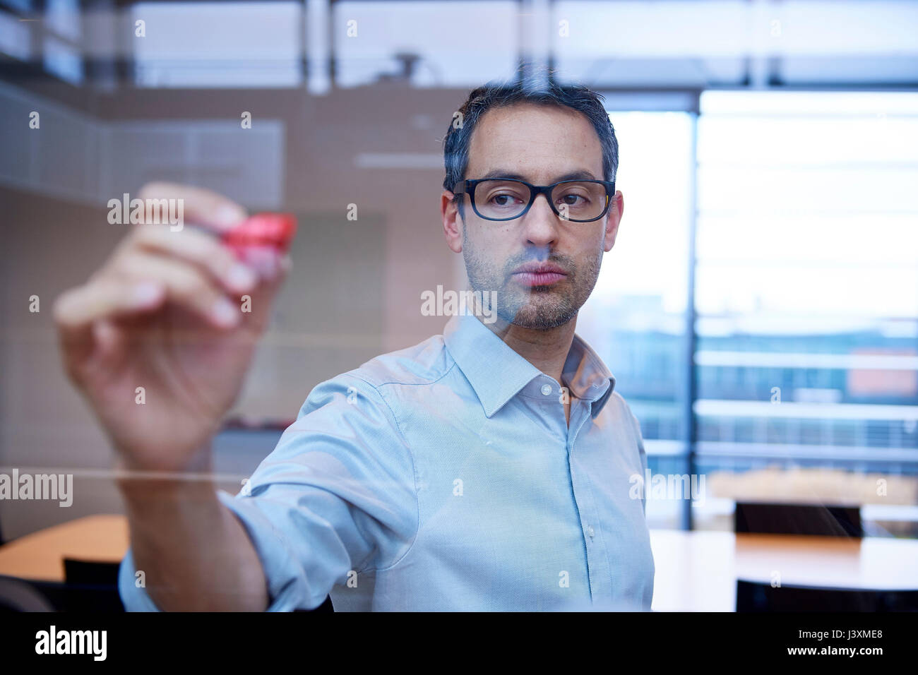 Businessman making presentation drawing graph on office window - Stock Image