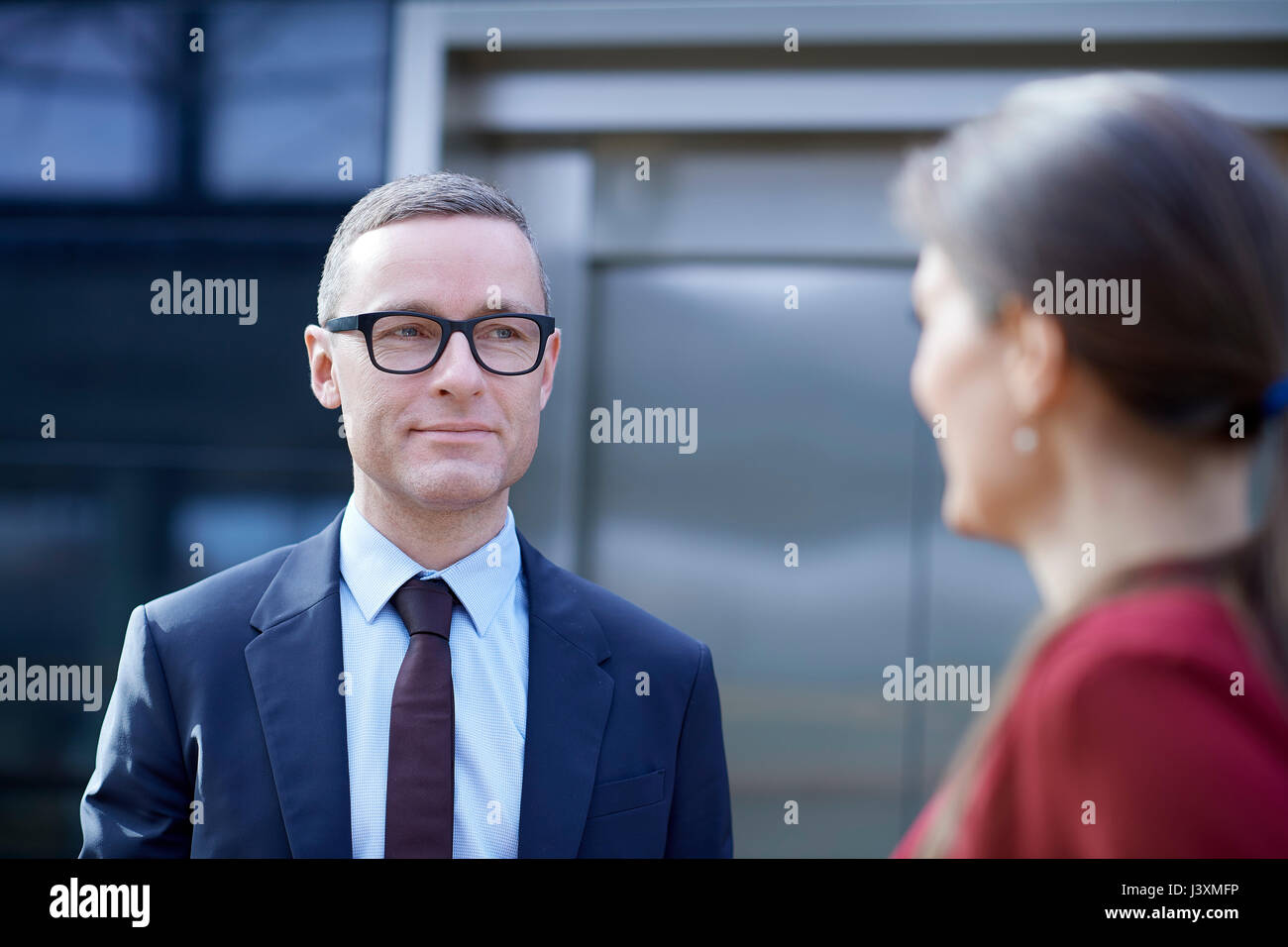 Over shoulder view of businessman approaching woman in office - Stock Image