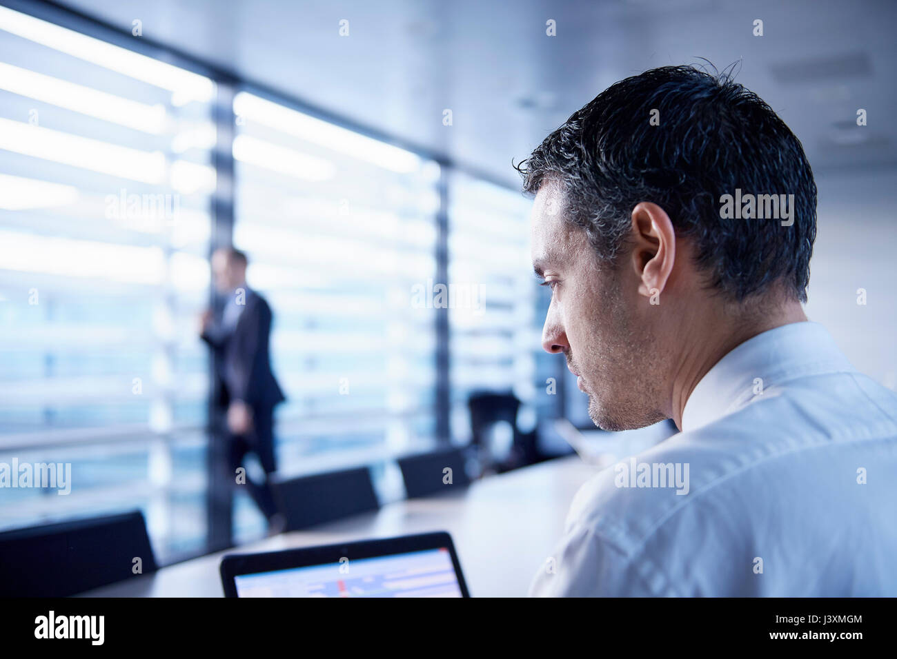 Businessman using laptop at boardroom table - Stock Image