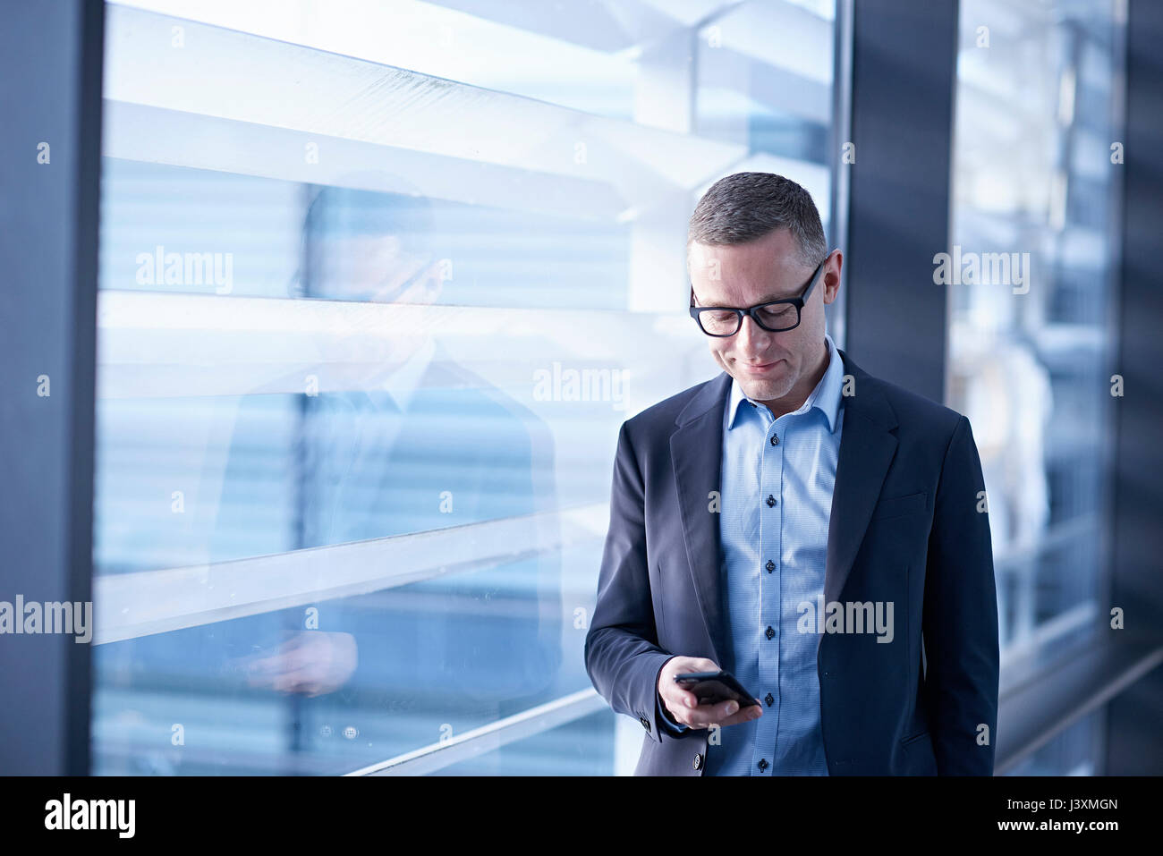 Businessman looking at smartphone in office - Stock Image