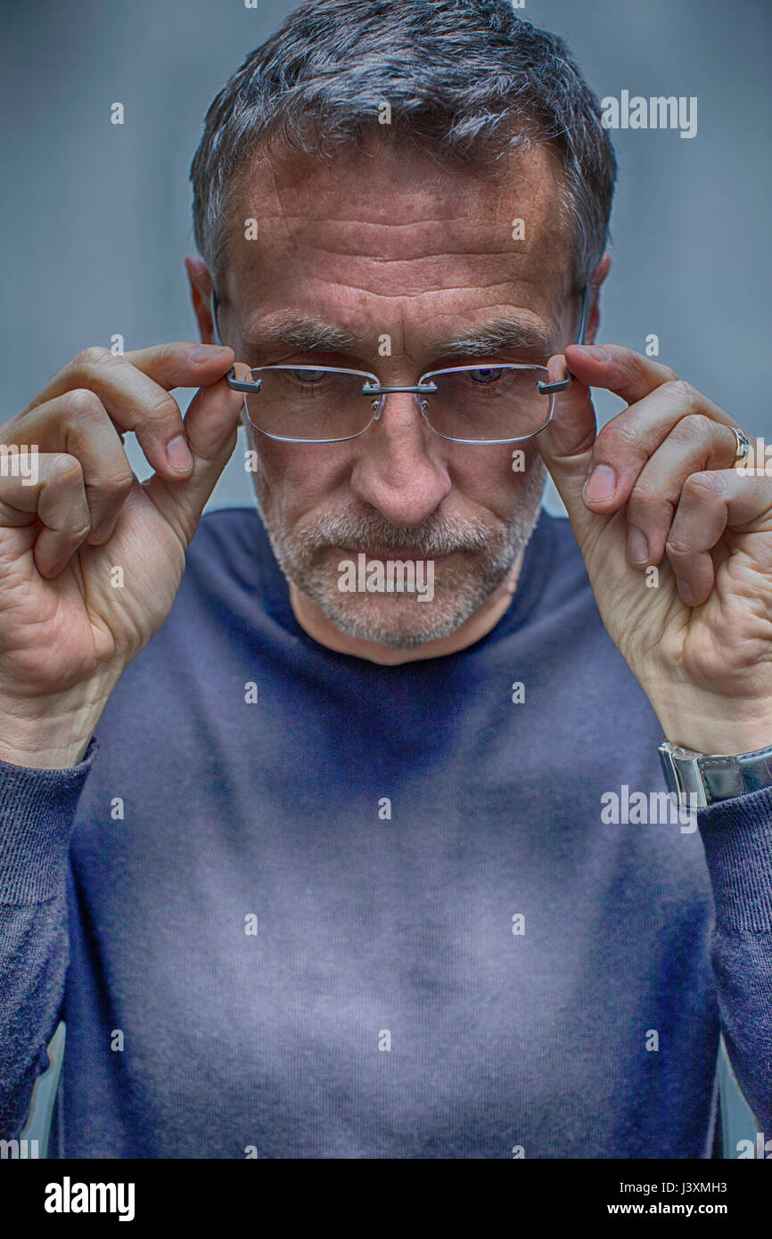 Portrait of greying mature man removing glasses - Stock Image
