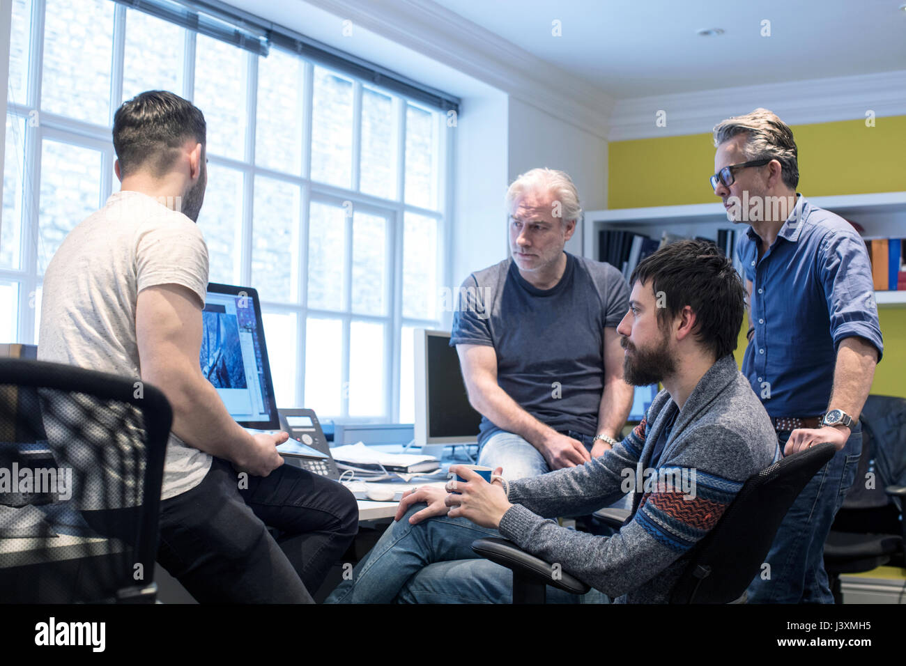 Colleagues in office using computer Stock Photo