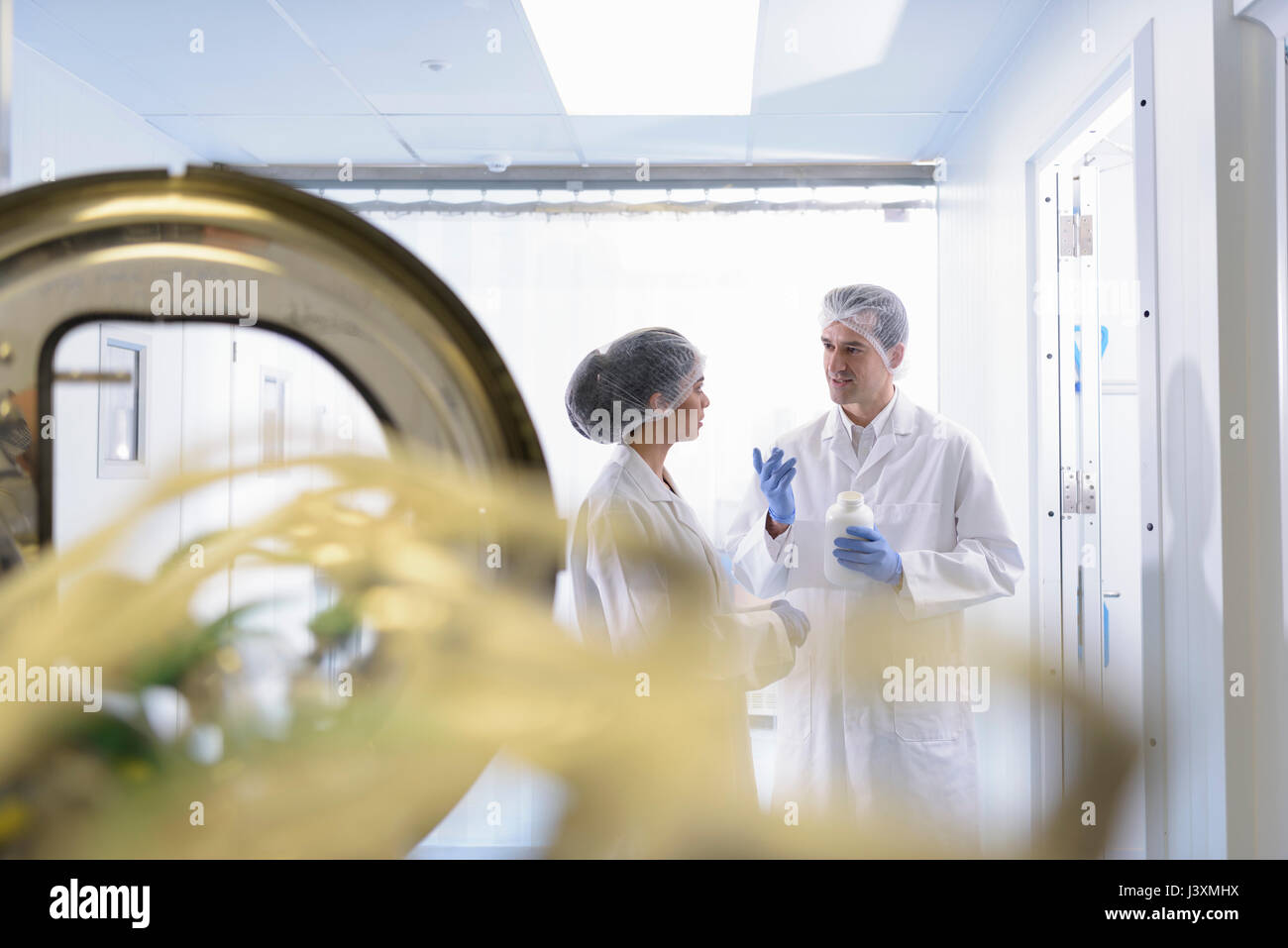 Workers in pill coating plant in pharmaceutical factory - Stock Image