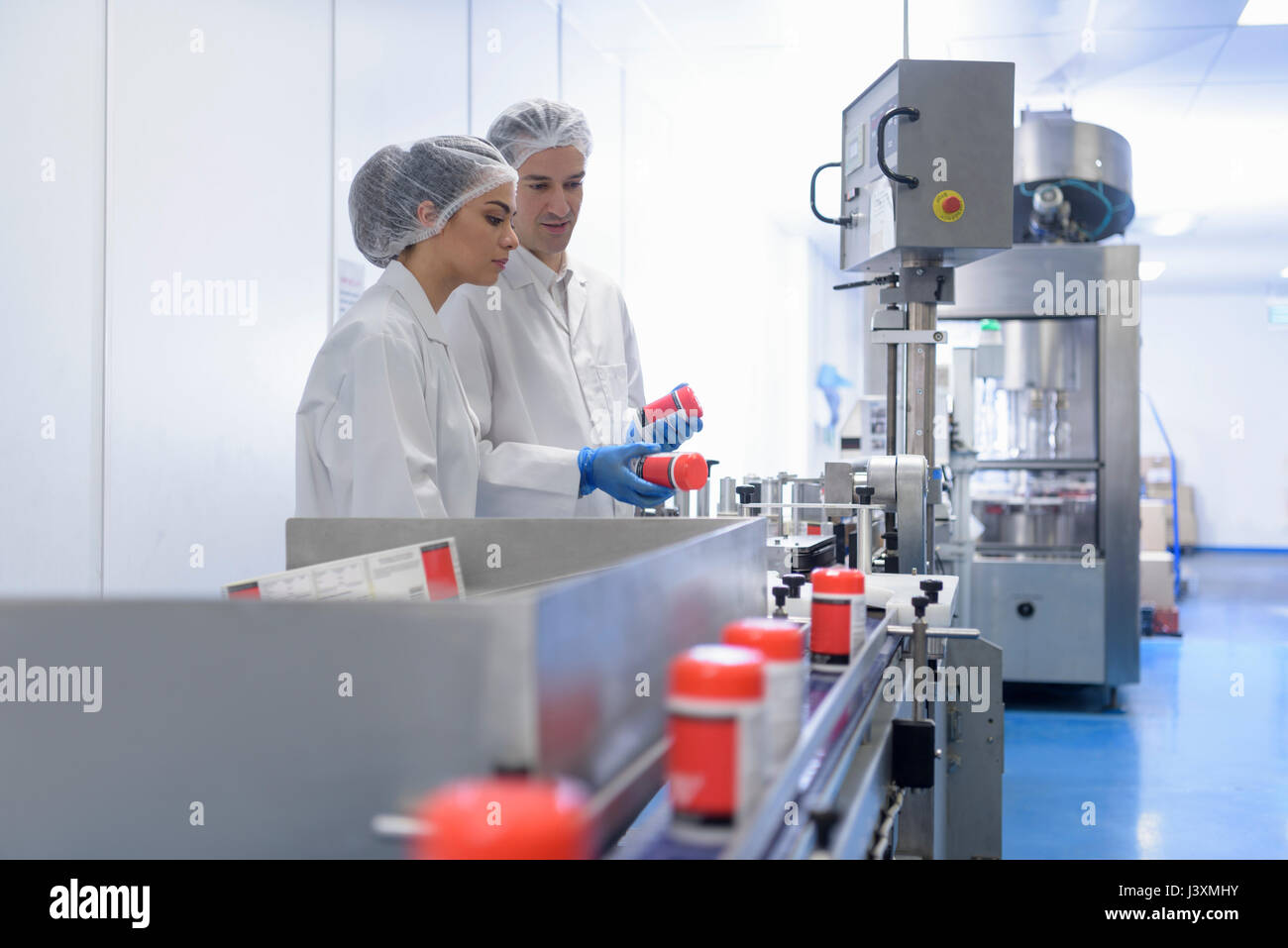 Workers on pill packing line in pharmaceutical factory - Stock Image