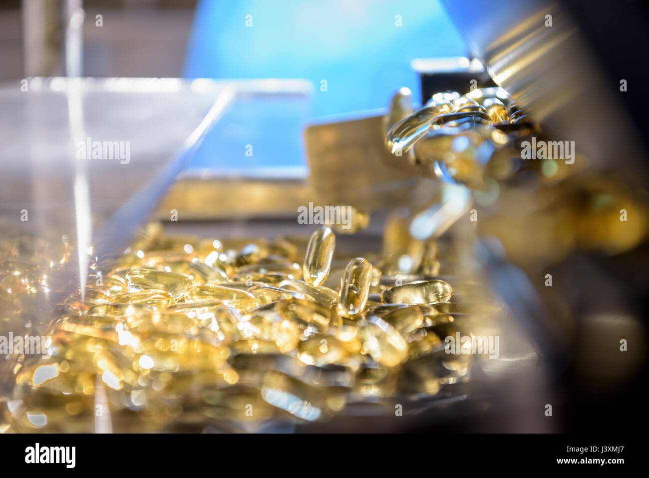 Capsules on production line in pharmaceutical factory - Stock Image