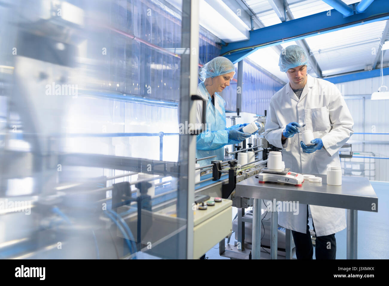 Workers on production line in pharmaceutical factory - Stock Image