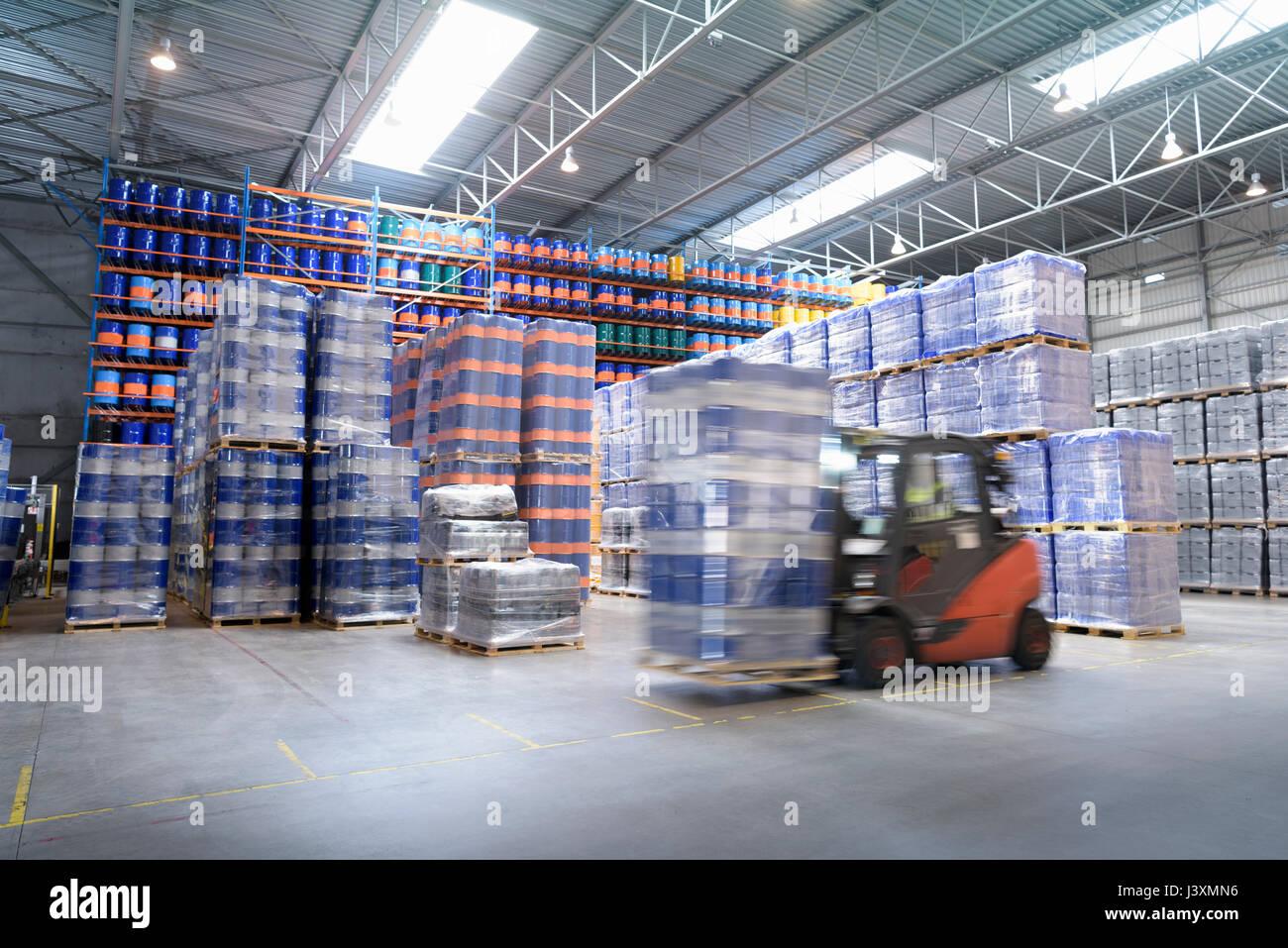 Forklift truck storing barrels in oil blending factory - Stock Image
