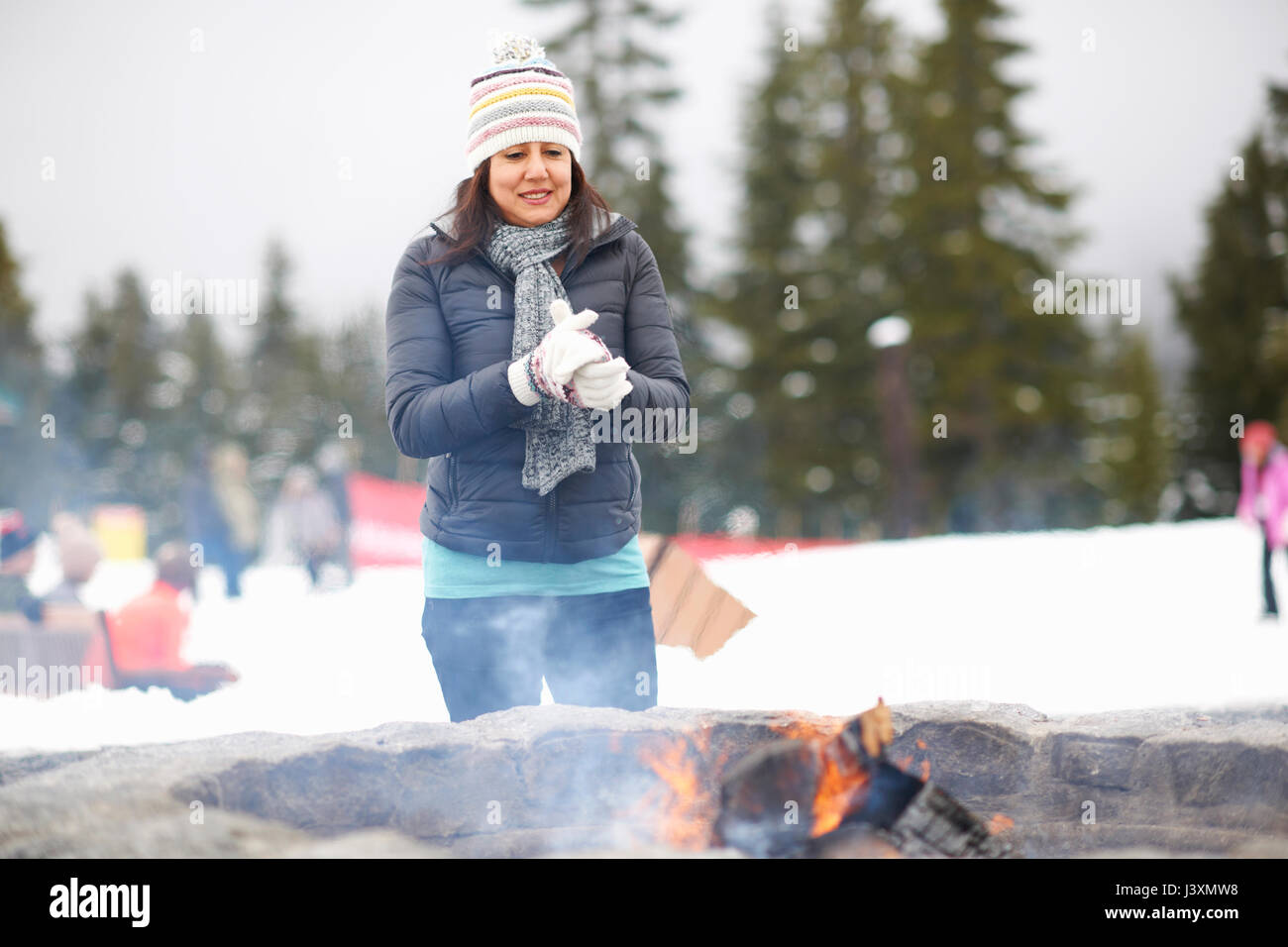 Woman warming by fire pit, Vancouver, Canada Stock Photo