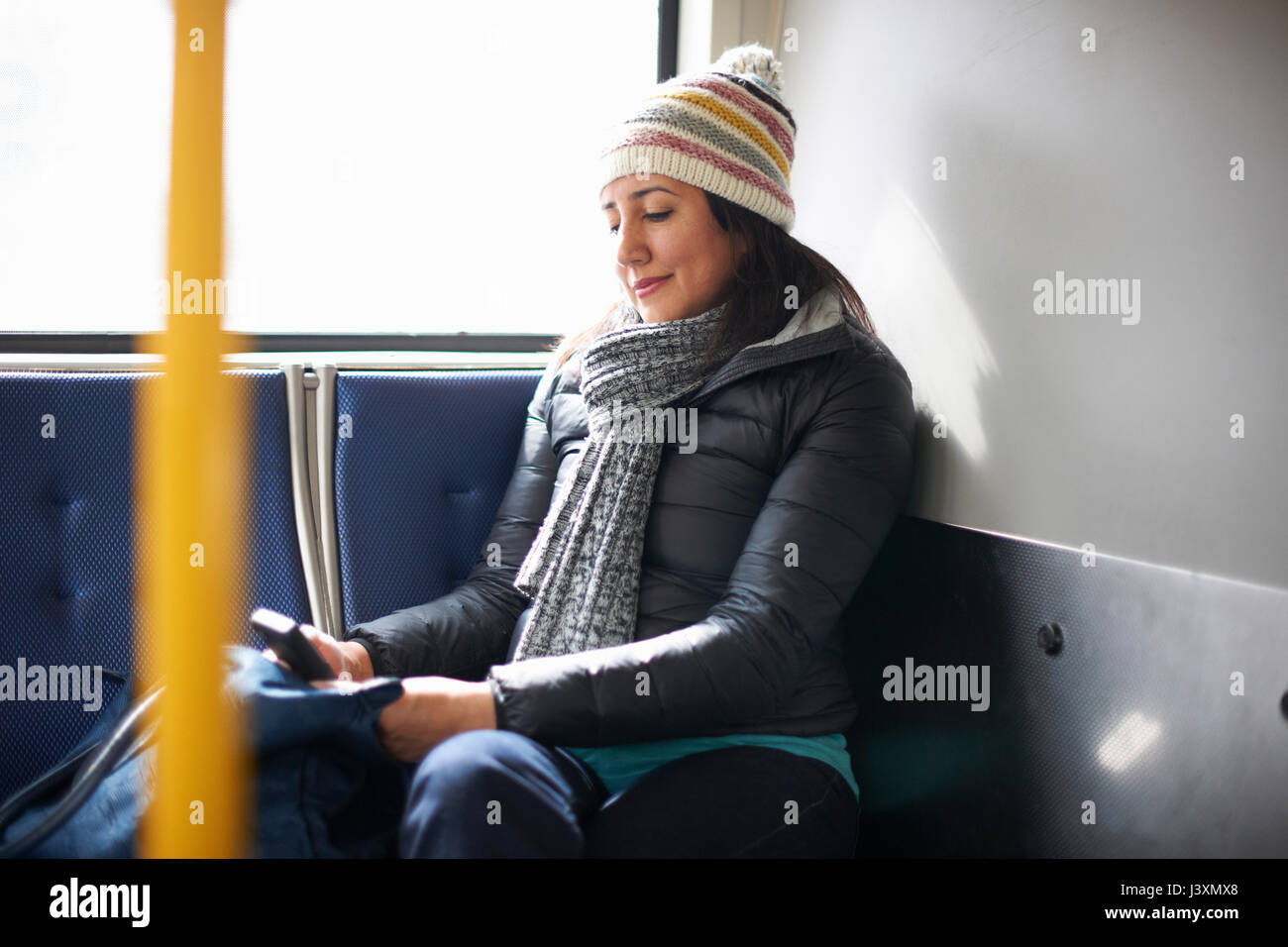 Woman travelling on bus looking at smartphone - Stock Image