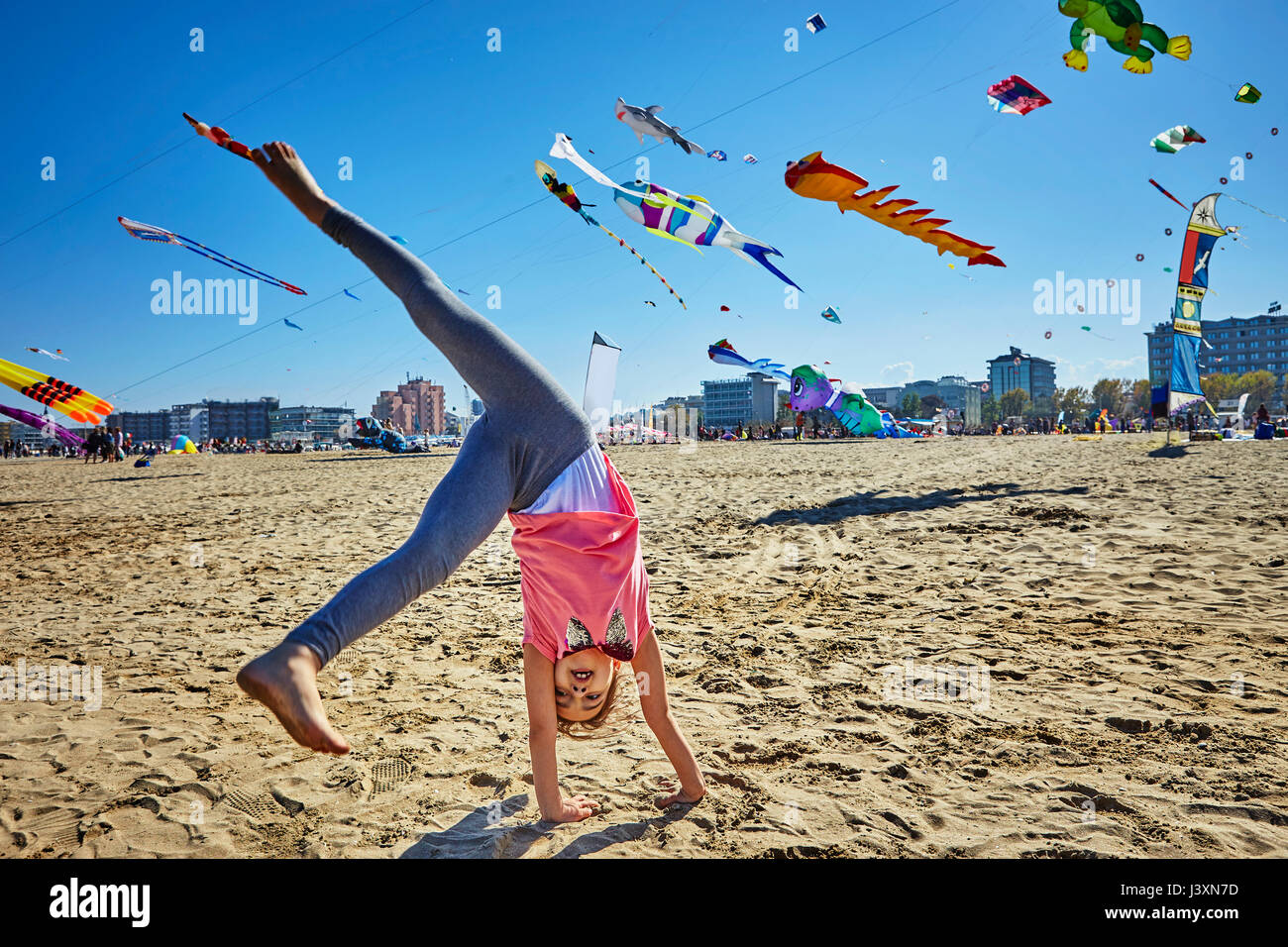 Young girl doing cartwheel on beach, kites flying in sky behind her, Rimini, italy - Stock Image