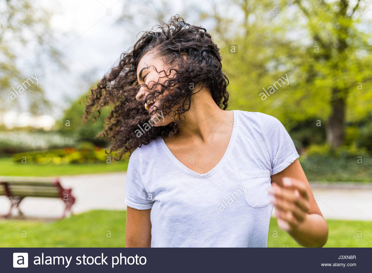 Young woman with long curly hair dancing in Battersea Park - Stock Image