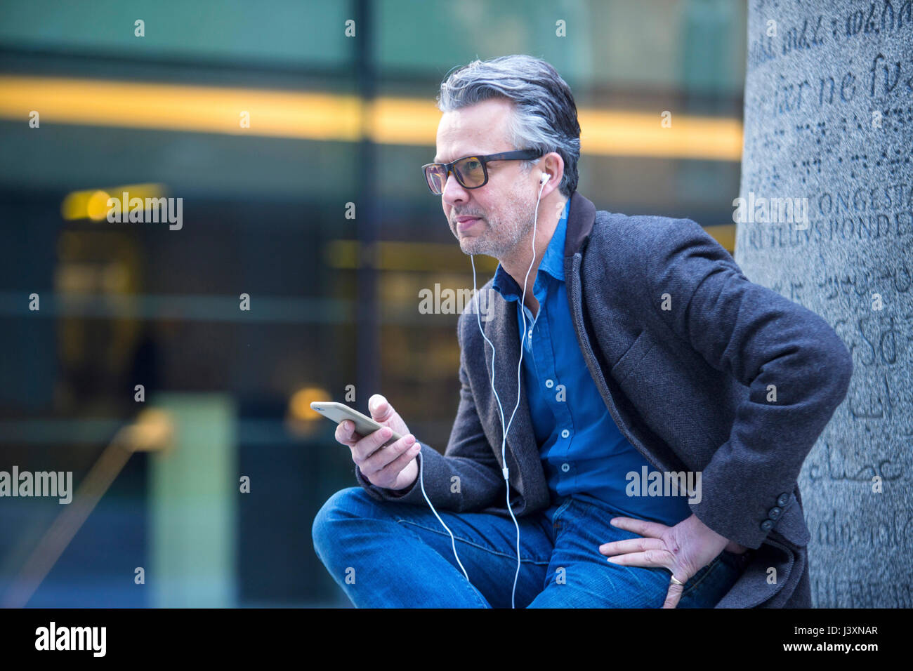 Man with smartphone and earbuds sitting outdoors - Stock Image