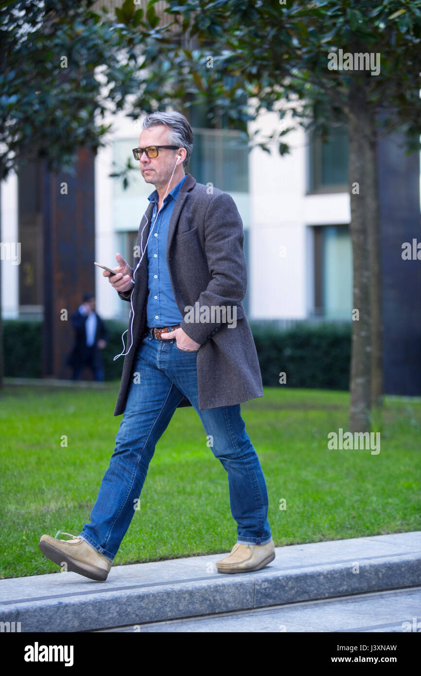 Man with smartphone and earbuds walking outdoors - Stock Image