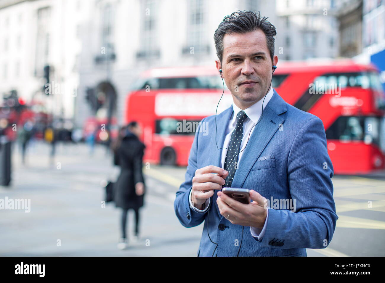 Businessmen in street with smartphone and earbuds, London, UK - Stock Image