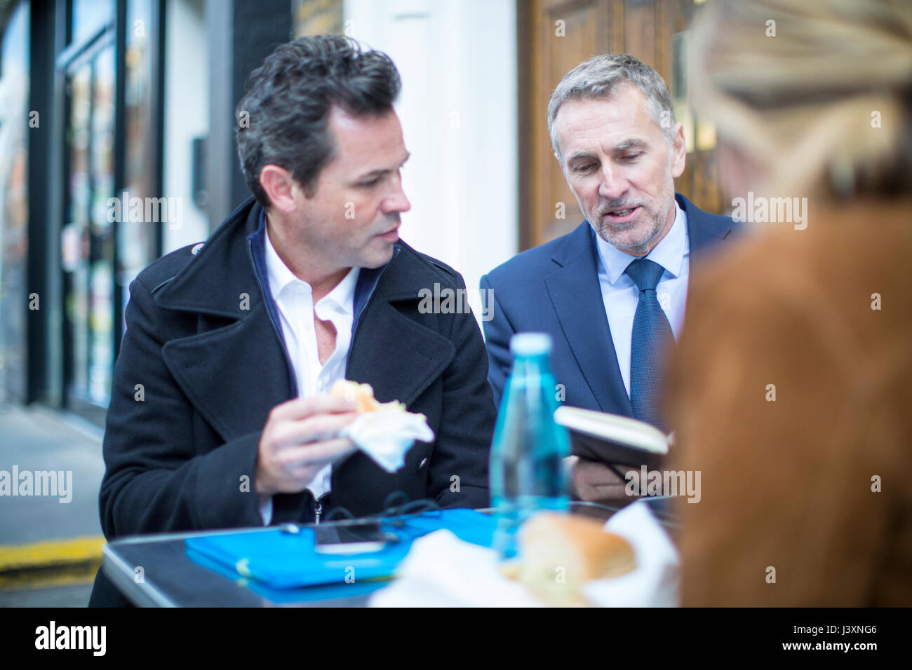 Businesspeople at pavement cafe having working lunch - Stock Image