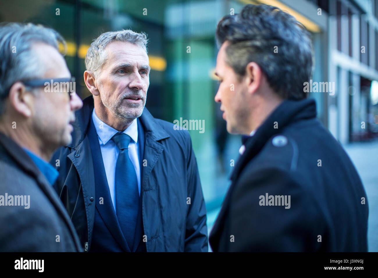 Businessmen in street talking - Stock Image