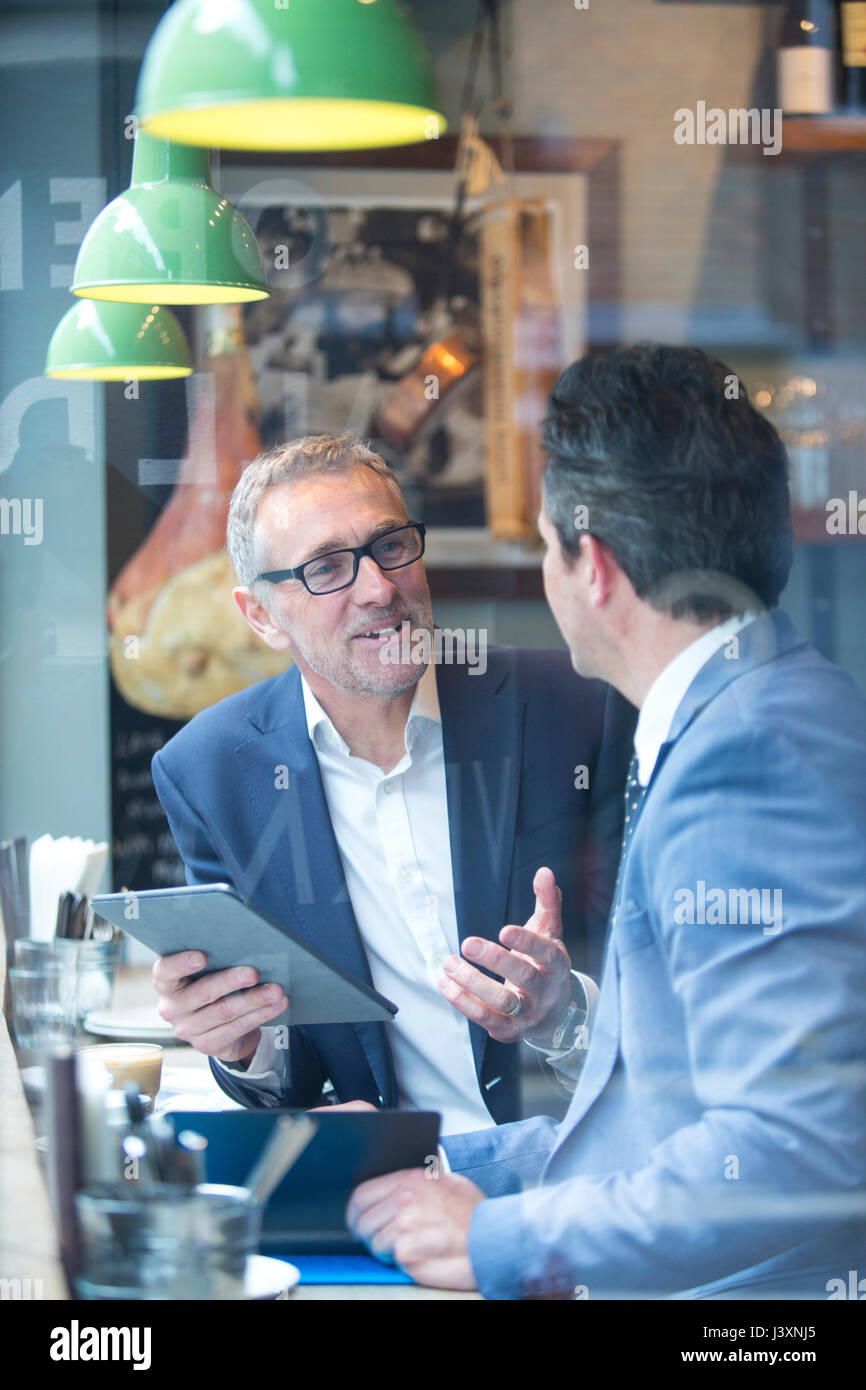 Two businessmen having discussion in restaurant window seat - Stock Image