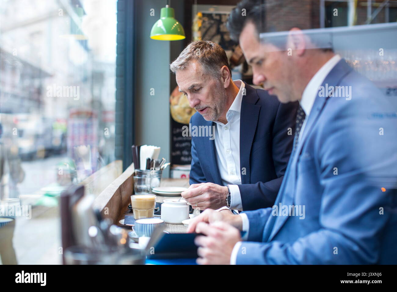 Two businessmen having working lunch in restaurant - Stock Image