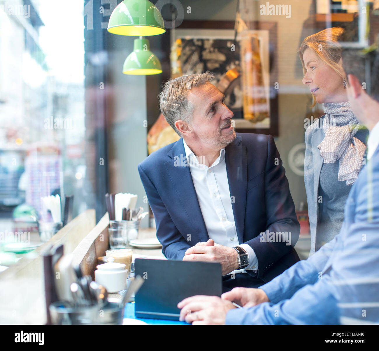 Businessmen and woman having working lunch in restaurant - Stock Image