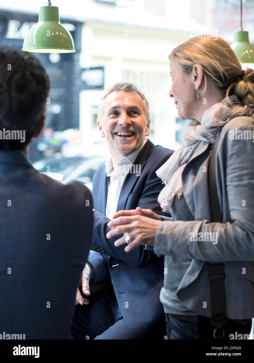 Businessmen and woman having discussion in restaurant - Stock Image