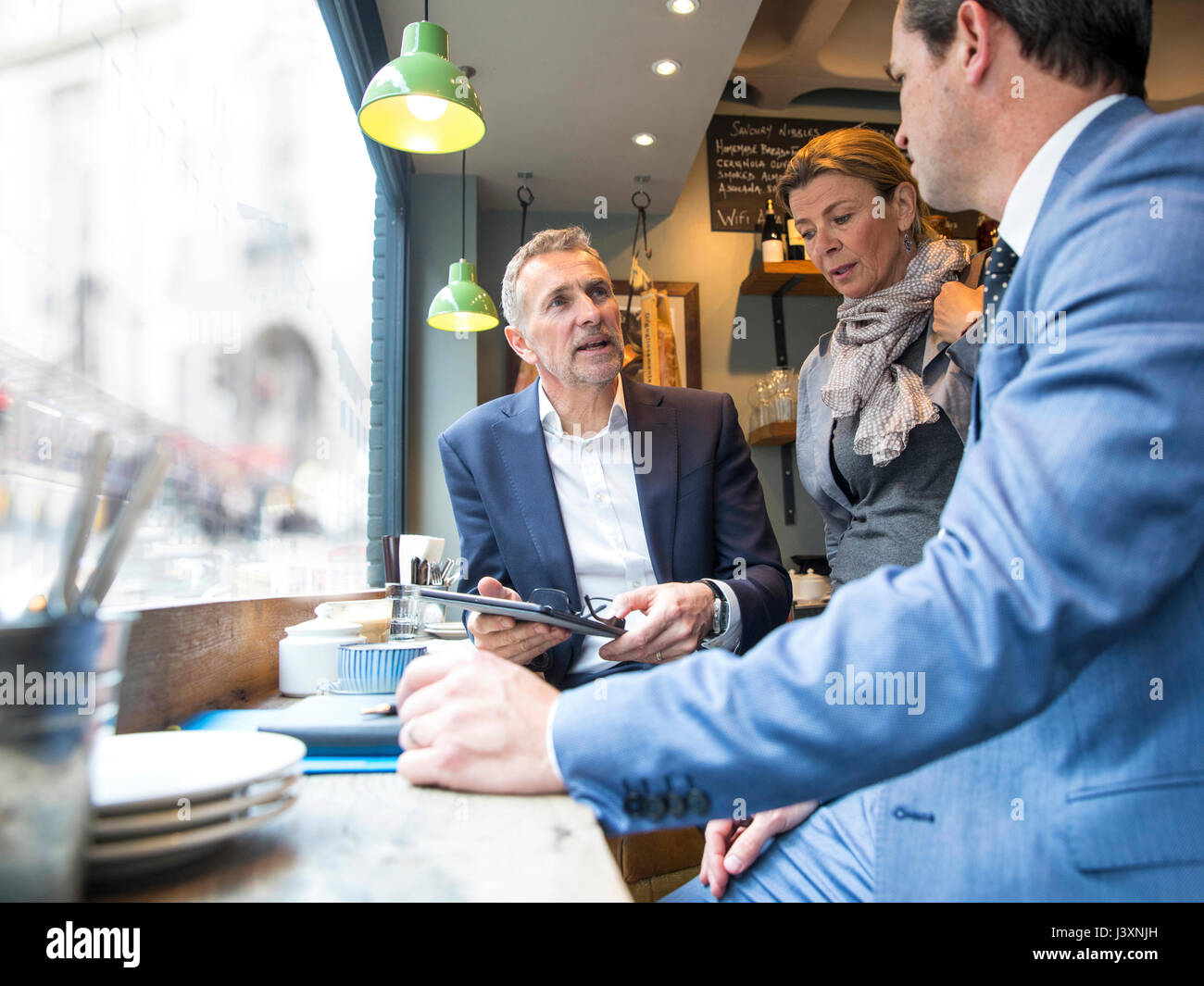Businessmen and woman having discussion in restaurant window seat - Stock Image