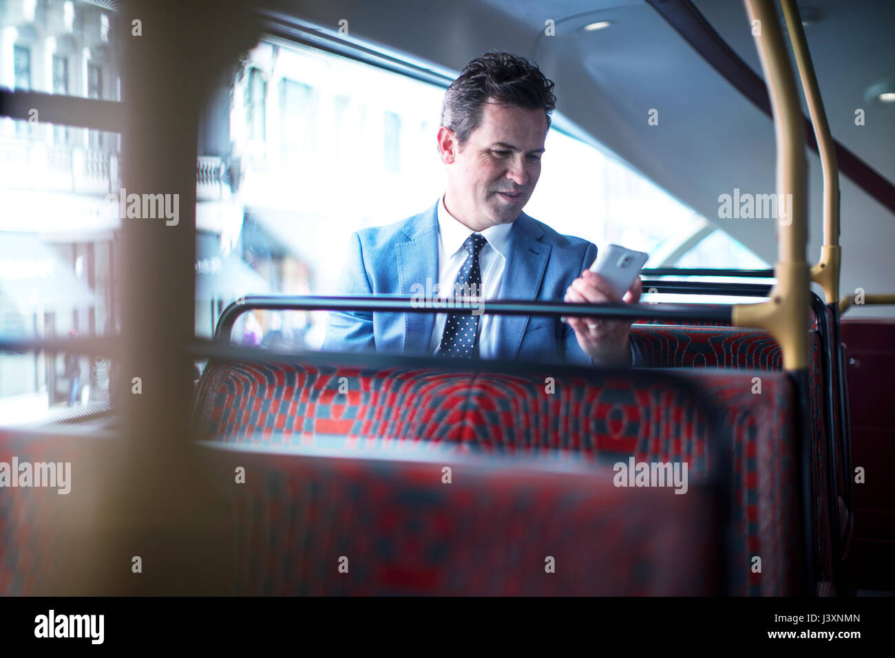Businessman looking at smartphone on double decker bus - Stock Image