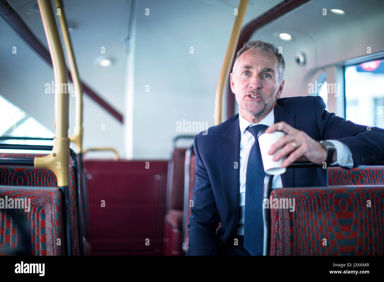 Businessman with takeaway coffee on double decker bus - Stock Image
