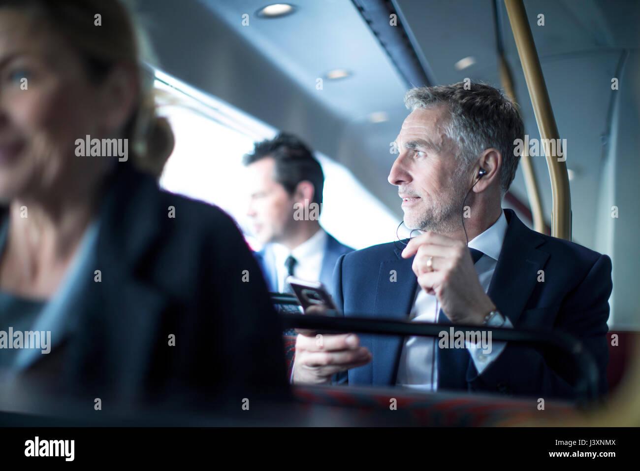 Businessman listening to smartphone earphones on double decker bus - Stock Image