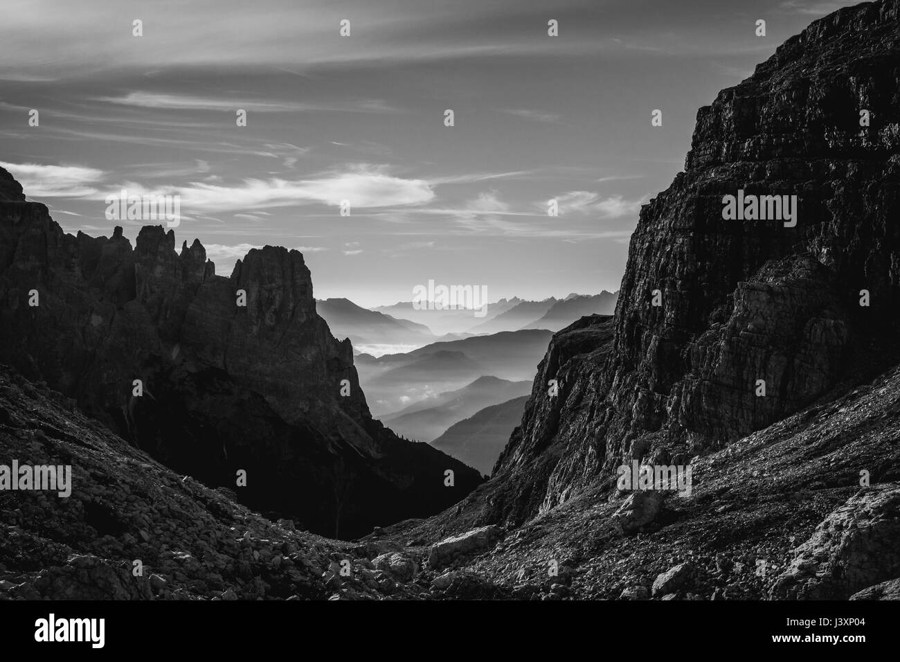 Black and white landscape view of hazy rolling mountains and hills in the Italian Dolomites at sunrise. Landscape - Stock Image