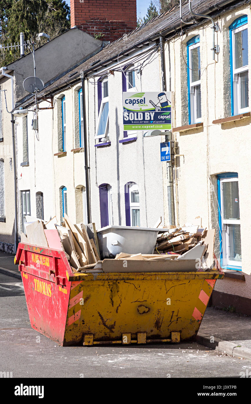 Waste skip containing a bath outside a sold sign on house, Abergavenny, Wales, UK - Stock Image