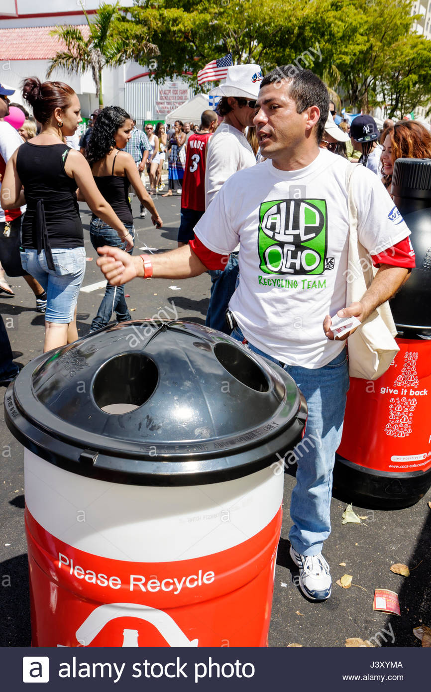 Miami Florida Little Havana Calle Ocho annual event festival street fair Hispanic man crowd plastic bottle recycling - Stock Image