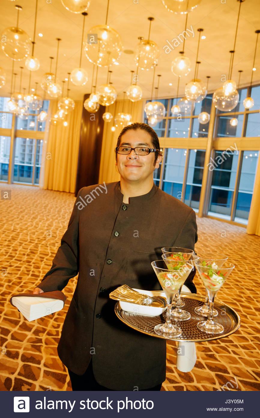 Miami Florida Epic Hotel luxury boutique waiter job Hispanic man uniform smiling hors d'oeuvres tray hospitality - Stock Image
