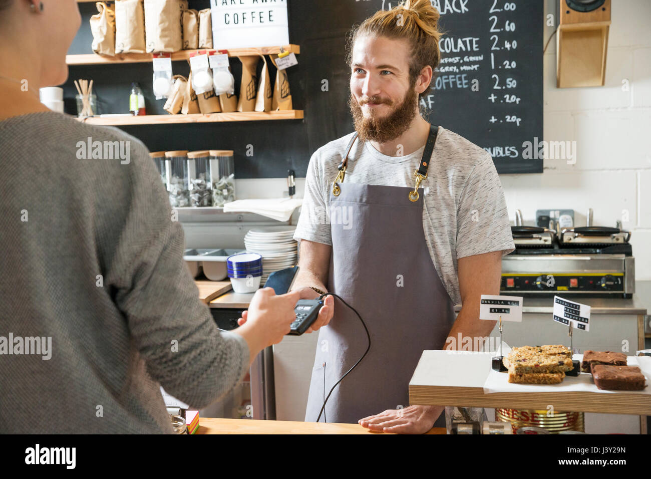 Customer paying contactless in a cafe at the counter - Stock Image