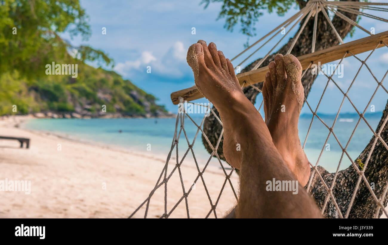 Men feet in Hammock, relaxing on the beach in Haad Rin, Ko Phangan - Stock Image