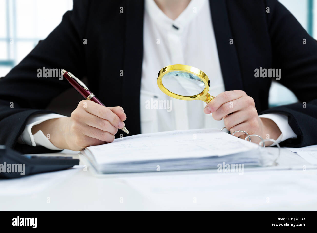 internal audit concept - woman with magnifying glass inspecting documents - Stock Image