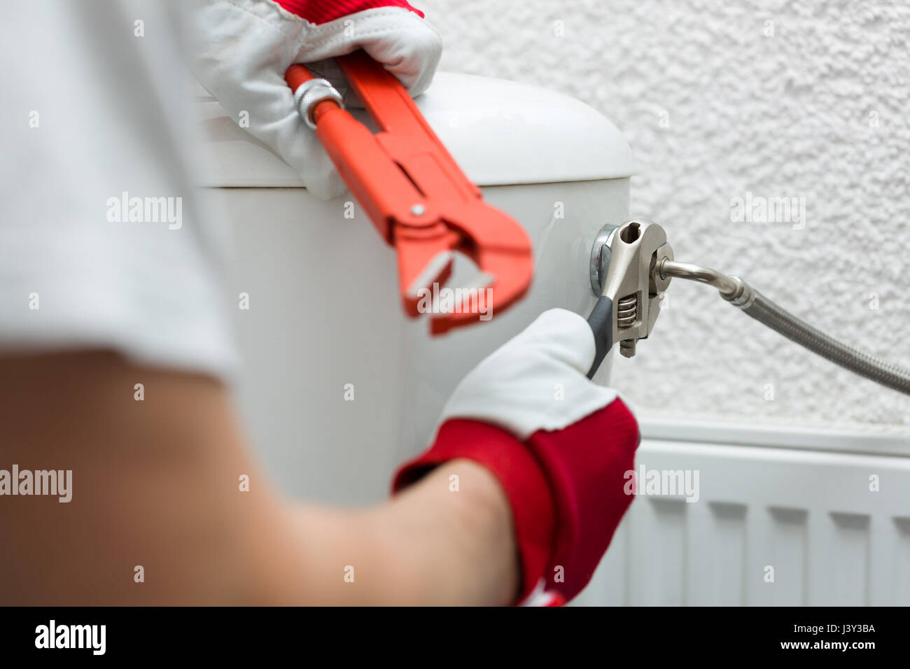 plumber installing pipe to water closet with wrench - Stock Image